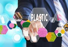 The businessman chooses PLASTIC on the virtual screen in plastic. Industrial network connection.The concept of raw material plastic in granules royalty free stock images