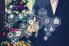 The businessman chooses the shopping cart on the touch screen, t. He backdrop of the Christmas tree and decorations. Special toning .Cyber Monday. Black Friday Stock Images