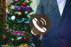 The businessman chooses telephone , VOIP on the touch screen, th. E backdrop of the Christmas tree and decorations. Special toning Stock Image