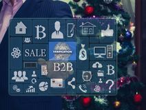 The businessman chooses VERIFICATION on the touch screen. The backdrop of the Christmas tree and decorations. Special toning . The concept of fingerprint Royalty Free Stock Photos