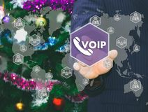 The businessman chooses VOIP on the touch screen. The backdrop of the Christmas tree and decorations. Special toning Stock Photo