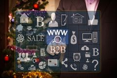 The businessman chooses www online searches on the touch screen, the backdrop of the Christmas tree and decorations. Special toni royalty free stock photo