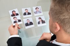 Businessman Choosing Candidate. Close-up Of Businessman Choosing Candidate In Office royalty free stock images