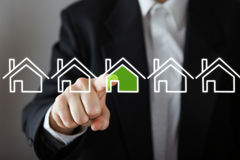 Businessman choosing house, real estate concept. Hand pressing the house icon. Copy space.  Stock Image