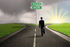 Businessman choosing path to success. Businessman is walking on the road with a sign of success or failure Royalty Free Stock Photo