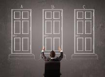 Businessman choosing the right door Stock Image
