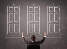 Businessman choosing the right door Stock Images