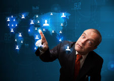 Businessman choosing from social network map Royalty Free Stock Photography