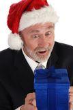 Businessman Christmas. Senior Businessman with Christmas gift and Santa Claus hat Royalty Free Stock Image