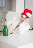 Businessman in Christmas cap with bottle at table Royalty Free Stock Photo