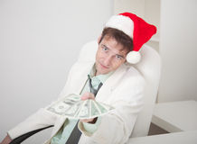 Businessman in Christmas cap gives us money Royalty Free Stock Photo