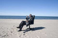 Businessman and cigar on beach Stock Image