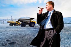 Businessman with cigar on industrial background Royalty Free Stock Image