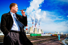 Businessman with cigar on industrial background Stock Images