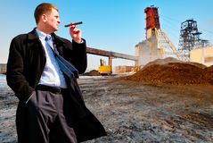 Businessman with cigar on industrial background Royalty Free Stock Images