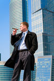 Businessman with cigar near skyscrapers Stock Photography