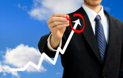 Businessman circling a rising arrow Stock Photography