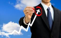 Businessman circling a rising arrow Stock Photography