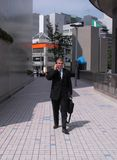 Businessman in a city. Businessman walking and discussing to the mobile phone Stock Image