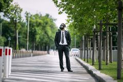 Businessman in the city wearing a gas mask. On the face Royalty Free Stock Image