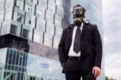 Businessman in the city wearing a gas mask on face. Royalty Free Stock Image