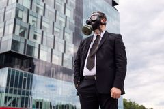Businessman in the city wearing a gas mask on face. Stock Photo