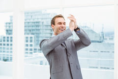 Businessman clapping hands in office Stock Photo