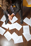 Businessman with clasped hands looking at documents scattered on floor Royalty Free Stock Photos