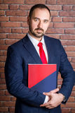 Businessman clasps a folder to his chest Royalty Free Stock Image