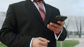 Businessman in classic suit is using smartphone outdoors stock video footage