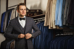 Businessman in classic vest against row of suits in shop. A young stylish man in a black cloth jacket. It is in the showroom, tryi royalty free stock photography