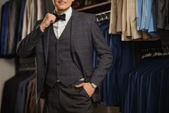 Businessman in classic vest against row of suits in shop. A young stylish man in a black cloth jacket. It is in the showroom, tryi stock image