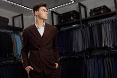 Businessman in classic vest against row of suits in shop. A young stylish man in a jacket. It is in the showroom, trying. Young man in classic vest against row royalty free stock images