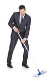 Businessman cleaning floor Stock Image