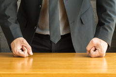 Businessman with clenched fist on the desk Royalty Free Stock Image