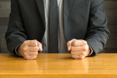 Businessman with clenched fist on the desk Stock Photos
