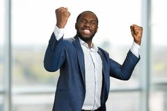 Businessman with clenched fists and teeth. Young manager clenching teeth and raised fists. Concept of great businessman achievement and victory Royalty Free Stock Image