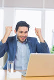 Businessman with clenched fists using laptop Royalty Free Stock Photography