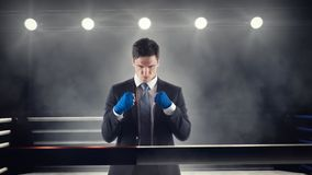 Businessman clenches wrapped fists in boxing ring Royalty Free Stock Photography