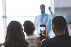 Businessman clicking photo with mobile phone in a business seminar. Rear view of young African-American businessman clicking photo with mobile phone in a stock photo