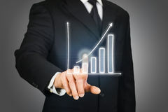 Businessman clicking on a rising chart Royalty Free Stock Images
