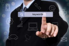 Businessman clicking search field with keywords. Business concept Stock Images
