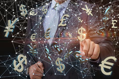 Businessman clicks on the dollar symbol on the background network. Royalty Free Stock Images