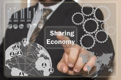 The businessman clicks on the Sharing Economy on the touch scree. N stock photo