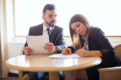 Businessman and client closing a deal. Good looking young businessman closing a deal with a female client while she signs a contract Stock Photo