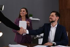 Businessman and client shaking hands over table with documents stock images
