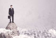 Businessman on cliff above labyrinth Stock Images