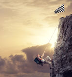 Businessman climb a mountain to get the flag. Achievement business goal and difficult career concept. Businessman climb a mountain with a rope to get the flag stock photo
