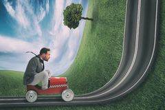 Businessman climb an uphill road with a small car. Difficult carrer concept. Man drives on a road bent upwards royalty free stock images