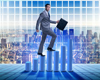 The businessman climbing bar charts in business concept Stock Photos